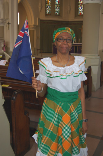 Lady dressed in traditional green coloured dress holds the Monseratt flag