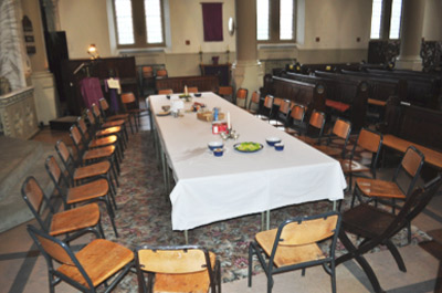 A long meeting table surrounded by chairs set up inside the church